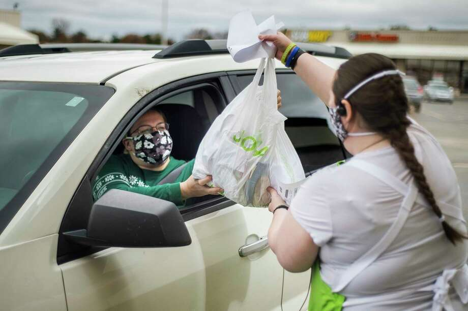 JoAnn Fabrics and Crafts employee Caitlin Hill, right, brings an order out to customer Kayla Schlicker, left, Monday at the store in Midland. (Katy Kildee/kkildee@mdn.net)