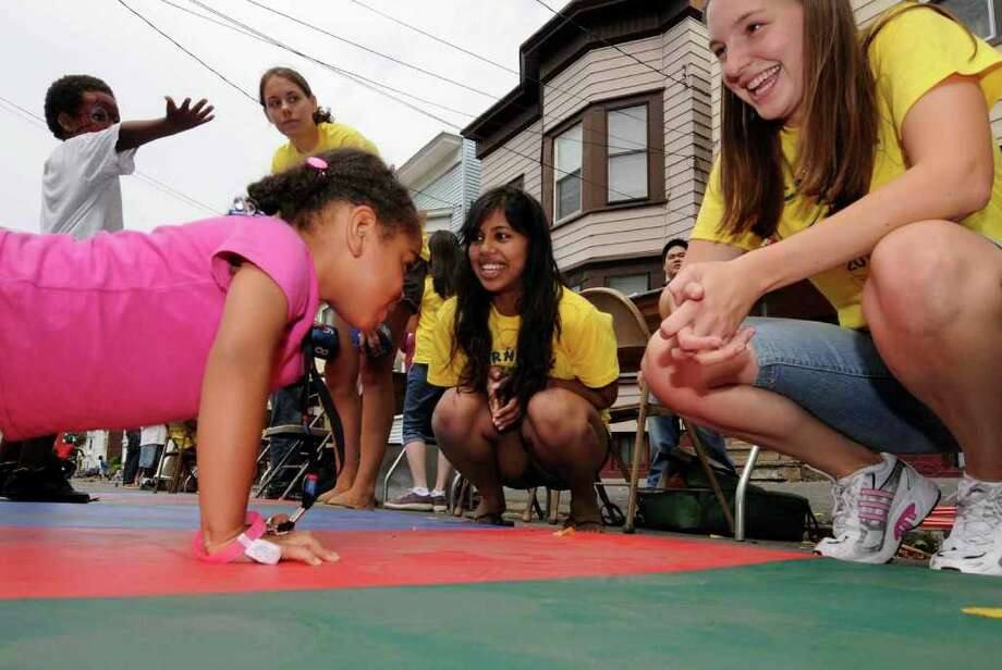 Four-year-old Nevaeh Sheldon of Albany impresses Albany Medical College  students Julie Westberg, right, and Sagarika Nag with her ability to do pushups at a physical fitness booth as part of Carnival on the Hill 2010 in Albany on Saturday.  ( Michael P. Farrell / Times Union ) Photo: Michael P. Farrell