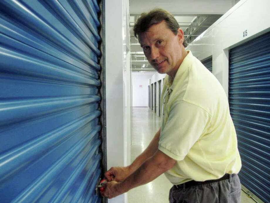 Mark Rekucki, president of Clifton Park Self Storage, turns a key in a red company lock on a storage unit on Thursday August 19, 2010. (Cathy Woodruff / Times Union)