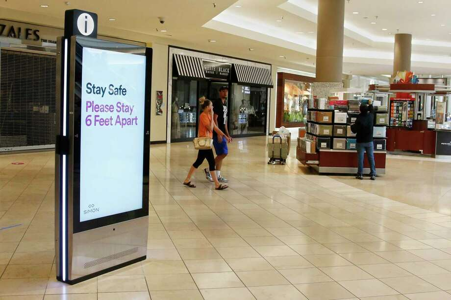 Signage encourages social distancing as Penn Square Mall reopens to the public Friday, May 1, 2020, in Oklahoma City. The mall has been closed since mid-March due to coronavirus concerns. (AP Photo/Sue Ogrocki) Photo: Sue Ogrocki / Associated Press / Copyright 2020 The Associated Press. All rights reserved.