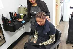 African American salon owners say they can't open without being allowed to offer blow drying — it's part of the service for black women's hair. Shown is Tasheba Taylor of Indigo Hair Innovations in West Hartford and Newington with a client.