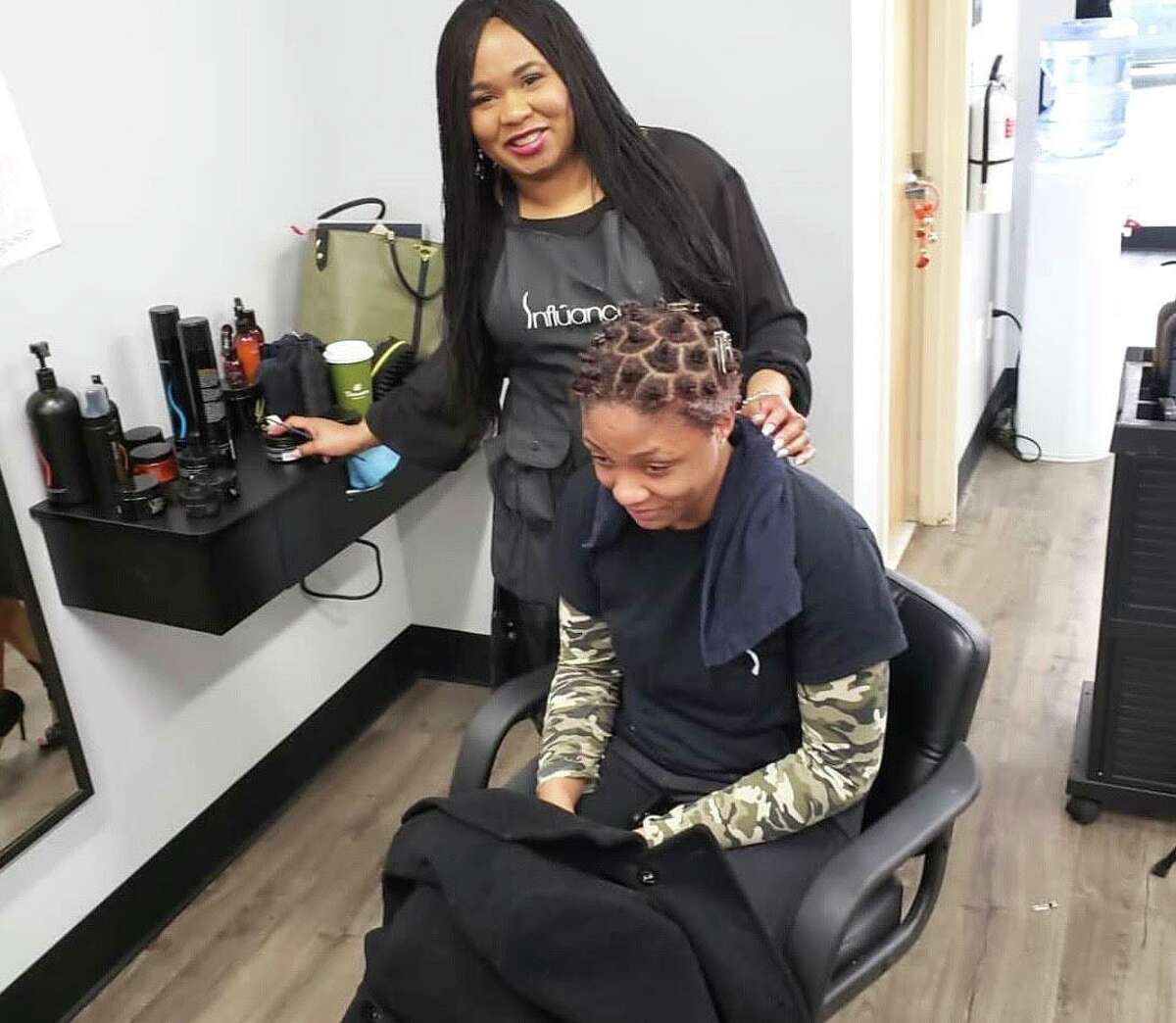 African American salon owners say they can't open without being allowed to offer blow drying - it's part of the service for black women's hair. Shown is Tasheba Taylor of Indigo Hair Innovations in West Hartford and Newington with a client.
