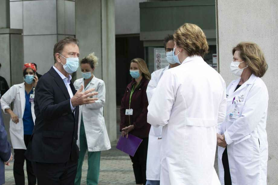 Gov. Ned Lamont, left, talks with medical staff outside Saint Francis Hospital, Thursday, May 7, 2020, in Hartford, Conn. He made a visit to the medical center to thank the healthcare workers for their efforts during the coronavirus pandemic. Photo: Mark Lennihan / Associated Press
