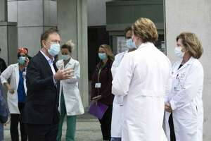 Gov. Ned Lamont, left, talks with medical staff outside Saint Francis Hospital, Thursday, May 7, 2020, in Hartford, Conn. He made a visit to the medical center to thank the healthcare workers for their efforts during the coronavirus pandemic.