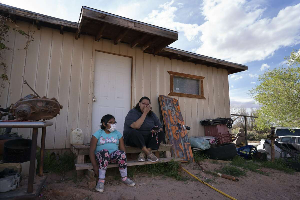 Angelina Dinehdeal wipes tears from her eyes as she sits with her 8-year-old daughter, Annabelle, on the family's compound in Tuba City, Ariz., on April 20, 2020. The family has been devastated by COVID-19. The Navajo reservation has some of the highest rates of coronavirus in the country. If Navajos are susceptible to the virus' spread in part because they are so closely knit, that's also how many believe they will beat it. (AP Photo/Carolyn Kaster)