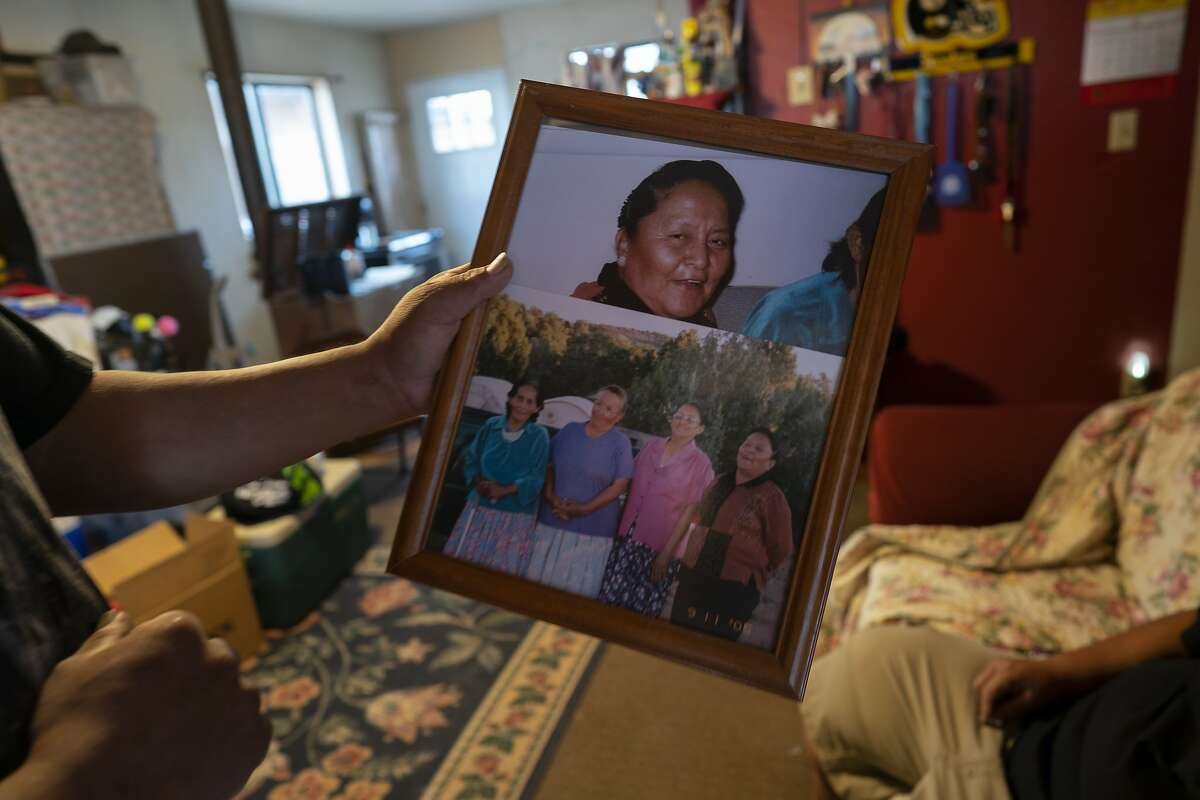Eugene Dinehdeal holds photos of family members, including Eva Dinehdeal at top, at the Dinehdeal family compound in Tuba City, Ariz., on the Navajo reservation on April 20, 2020. Eva Dinehdeal died of COVID-19 on April, 11, 2020. (AP Photo/Carolyn Kaster)