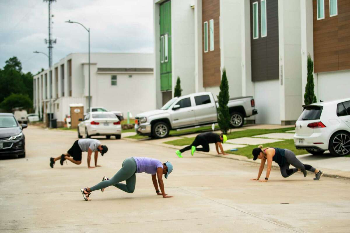 Neighbors do a series of exercises in their street, Thursday, May 7, 2020, in Houston. The neighbors have started coordinating group workouts winding through the community's streets, creating stations in participating driveways encouraging participants to do a series of exercises before running to the next station.