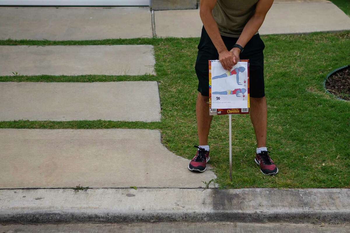 A signs for twenty pushups is pushed into the ground at the end of a driveway, Thursday, May 7, 2020, in Houston. The neighbors have started coordinating group workouts winding through the community's streets, creating stations in participating driveways encouraging participants to do a series of exercises before running to the next station.