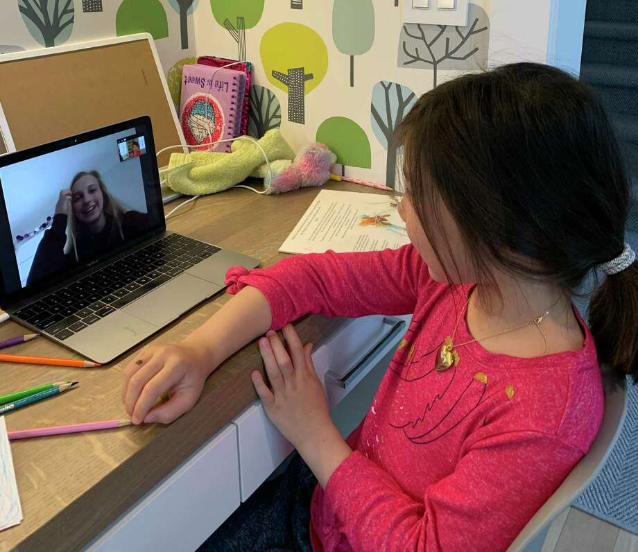 Sara Kaiser, a 10th grader at New Canaan High School and member of Homework Helpers, works online with her student, Samantha Michaud, a first grader at South School. Photo: Contributed Photo / New Canaan Advertiser Contributed
