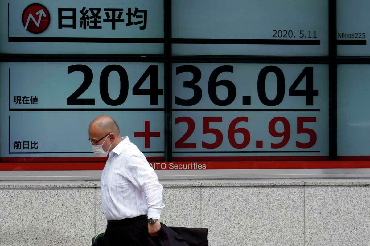 A man wearing a face mask walks past an electronic stock board showing Japan's Nikkei 225 index at a securities firm in Tokyo Monday, May 11, 2020. Asian stock markets are higher after Wall Street advanced as investors looked past dismal U.S. jobs and other data toward hopes for a global recovery from the coronavirus pandemic.(AP Photo/Eugene Hoshiko)