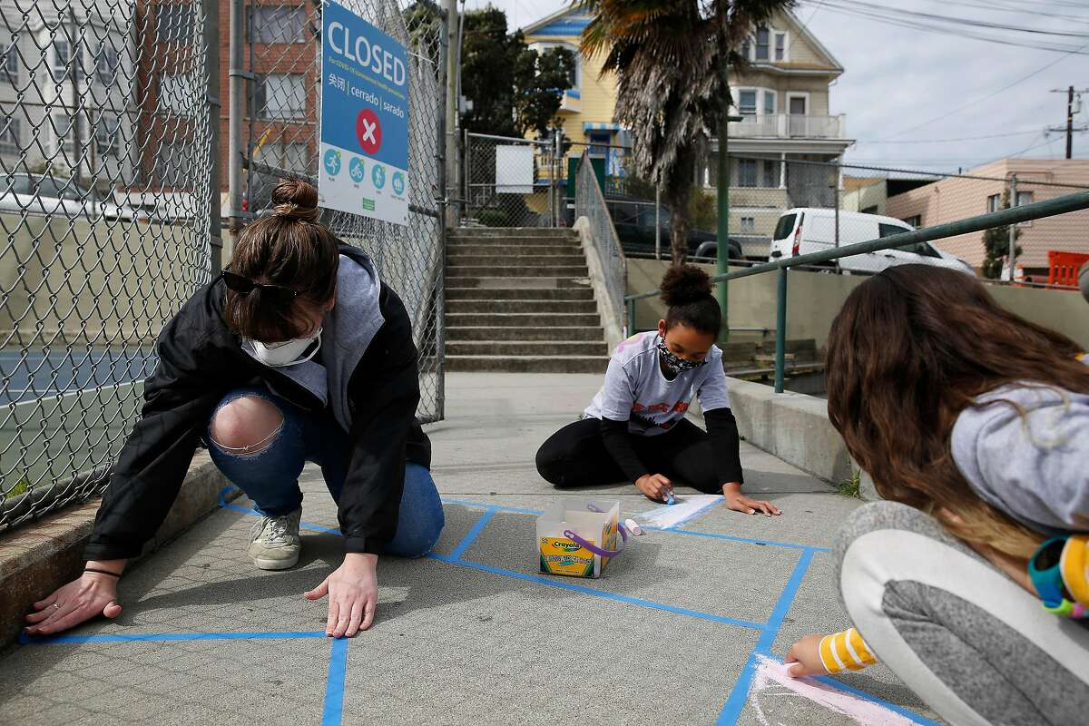 Caitlin Reilly (left), site lead for emergency child care center at Excelsior Playground, lays masking tape on the ground so children attending the emergency child care center can color between lines of the tape while remaining socially distant at the Excelsior Playground on Monday, May 11, 2020 in San Francisco, Calif.