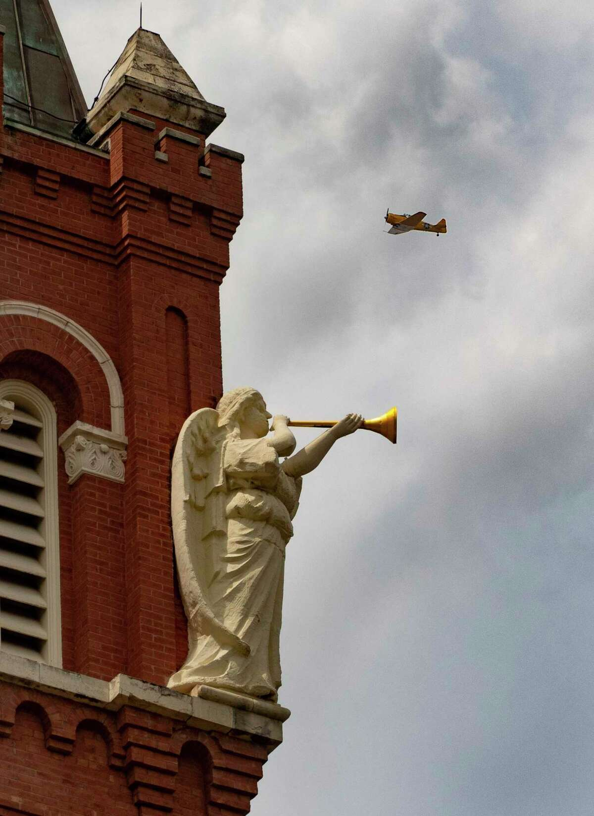 San Antonio Archbishop Gustavo Garcia-Siller flies over The University of Incarnate Word chapel in a vintage 1942 SNJ Texan airplane of the Tex Hill Wing of the Commemorative Air Force on Monday.