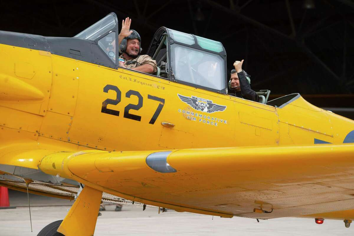 Garcia-Siller waves as he and pilot Darren Bond prepare to take off in the bright yellow plane, which was built to train Navy pilots in World War II.