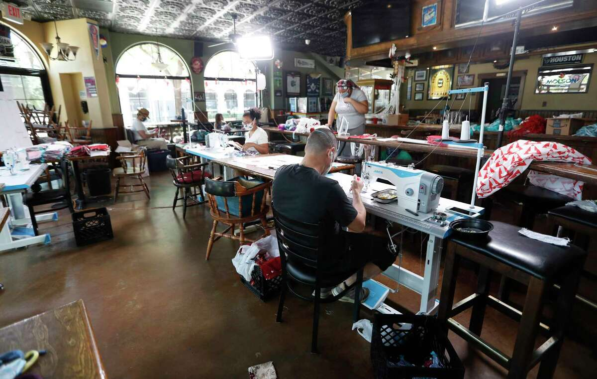 People work on producing masks inside of the Maple Leaf Pub, in Houston, Thursday, May 7, 2020. Courtney Wyckoff and Micahl Wyckoff started making masks out of their home after both finding themselves out of work because of coronavirus. Courtney, a seamstress, used leftover fabric she had lying around the house to start making the mask. They also started hiring their other out of work friends to help them.Their business is Grab Bag Masks.com.