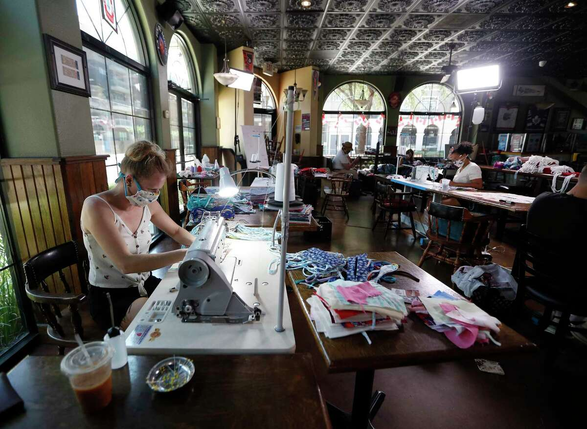 Courtney Wyckoff sews masks inside of the Maple Leaf Pub, in Houston, Thursday, May 7, 2020. Courtney and her husband Micahl started making masks out of their home after both finding themselves out of work because of coronavirus. Courtney, a seamstress, used leftover fabric she had lying around the house to start making the mask. They also started hiring their other out of work friends to help them. Their business is Grab Bag Masks.com.