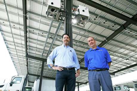 Big Sun Solar owners Robert Miggins, left, and Jason Pittman show off the solar panel arrangement last Wednesday that was installed at Rush Enterprises Truck Facility.