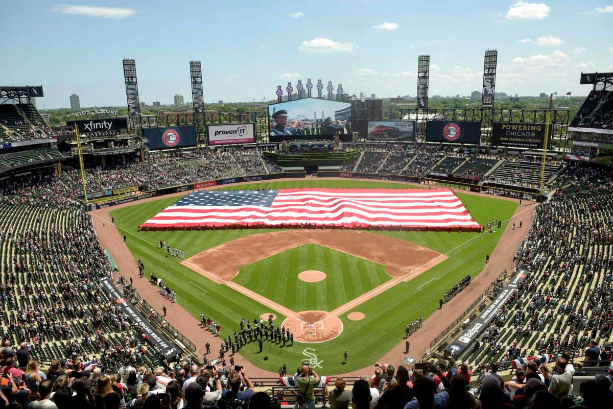 FILE - In this July 4, 2019, file photo, an American Flag is unfurled in the outfield during the playing of the National Anthem before the start a baseball game between the Chicago White Sox and the Detroit Tigers in Chicago. Major League Baseball owners gave the go-ahead Monday, May 11, 2020, to making a proposal to the playersa€™ union that could lead to the coronavirus-delayed season starting around the Fourth of July weekend in ballparks without fans, a plan that envisioned expanding the designated hitter to the National League for 2020. (AP Photo/Mark Black, File)