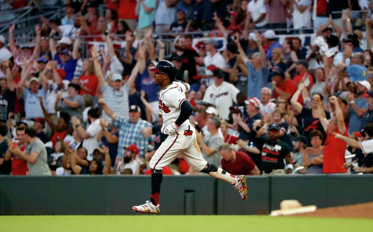 FILE - In this July 4, 2019, file photo, Atlanta Braves' Ozzie Albies rounds first base after hitting a three-run home run during the third inning of the team's baseball game against the Philadelphia Phillies in Atlanta. Major League Baseball owners gave the go-ahead Monday, May 11, 2020, to making a proposal to the playersa€™ union that could lead to the coronavirus-delayed season starting around the Fourth of July weekend in ballparks without fans, a plan that envisioned expanding the designated hitter to the National League for 2020. (AP Photo/John Bazemore, File)