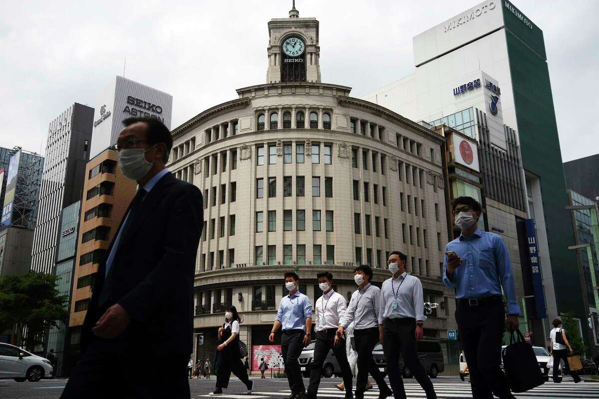 People wearing face masks to help curb the spread of the coronavirus walk at Ginza shopping district in Tokyo Tuesday, May 12, 2020. Japan is still under a coronavirus state of emergency which was extended until the end of May though there have been no hard lockdowns.