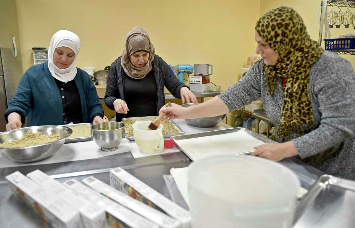 """New Haven, Connecticut - Wednesday, February 6, 2019: Faten Natfai of Syria, Hala Ghali of Syria, and Nieda Abbas of Iraq, left to right, making baklava at Katalina's bakery on Whitney Ave. in New Haven for Yale """"butteries"""", late night cafe's at Yale are refugee chefs sponsored by Integrated Refugee and Immigrant Services."""