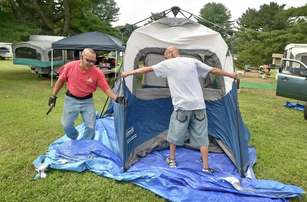 Madison, Connecticut - Friday, August 31, 2018: Noel Figuero of Hartford, left, and friend Teddy Rivera, camping together as a tradition with their friends and families at Hammonasset State Park in Madison for the last 18-years on both Labor Day Weekend and Memorial Day weekend, set up their weekend camp Friday. Because of coronavirus concerns, the 2020 camping season at state parks will be delayed to June 11.