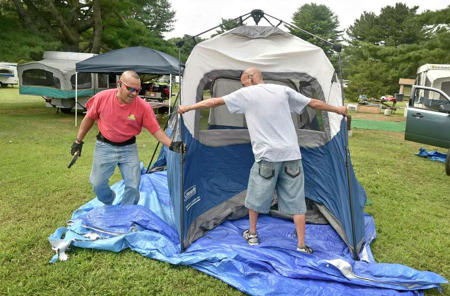 Madison, Connecticut - Friday, August 31, 2018: Noel Figuero of Hartford, left, and friend Teddy Rivera, camping together as a tradition with their friends and families at Hammonasset State Park in Madison for the last 18-years on both Labor Day Weekend and Memorial Day weekend, set up their weekend camp Friday. Because of coronavirus concerns, the 2020 camping season at state parks will be delayed to June 11. Photo: Peter Hvizdak / Hearst Connecticut Media / New Haven Register