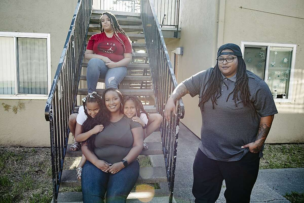 Raven Winchester, right, poses for a portrait with her wife Symphony Luna, and daughters Malien Lindsy, Kataleya Lindsy and Anjalena Lindsy, outside their home in Oakland, Calif, on Friday, May 1, 2020. After years of custodial work, Winchester enrolled for Flockjay.com's tech sales courses, and is now a sales rep at the very company where she used to scrub toilets.