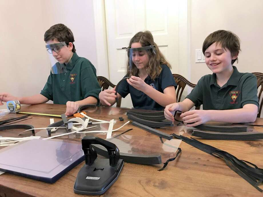 Christopher, Caera and Kevin Cope, all three Scouts from Troops 53 and 219, work together around the family table to make protective face shields for community healthcare workers. Photo: Contributed