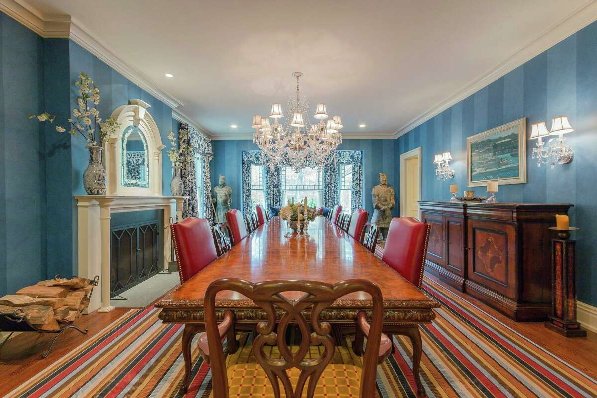 The banquet-sized formal dining room features a fireplace and a snowflake-cut crystal chandelier designed by Ralph Lauren.