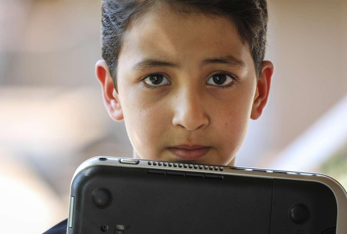 Yousuf Durrani, de ochoaños, posa junto a la laptop que utiliza para hacer sus tareas escolares en el apartamento de su familia en el área de Gulfton, en Houston. Yousuf comparte la misma computadora personal junto a su hermano y las dos hermanas de ambos mientras las escuelas permanecen cerradas debido a la pandemia del COVID-19.