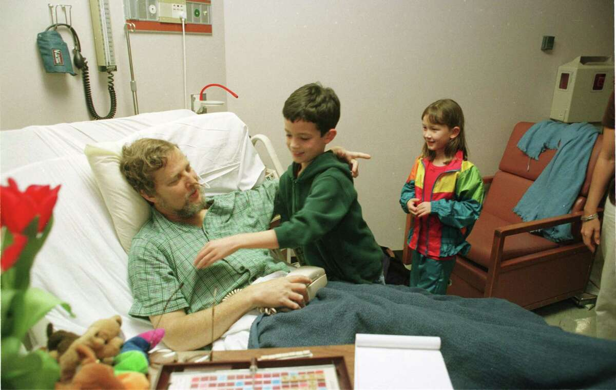 Mike Snyder plays with young visitors while awaiting his 1998 liver transplant.