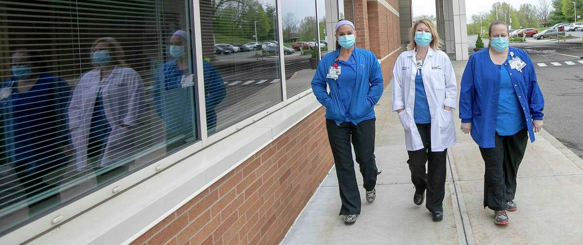 Left to right, Jenn Kolakoski, Pavilion D nurse manager, Tara Zane, Pavilion B nurse manager, and Lori Nohilly, director of inpatient nursing and critical care, walk the grounds on a break Friday, May 8, 2020 at MidState Medical Center in Meriden. (Dave Zajac/Record-Journal via AP)