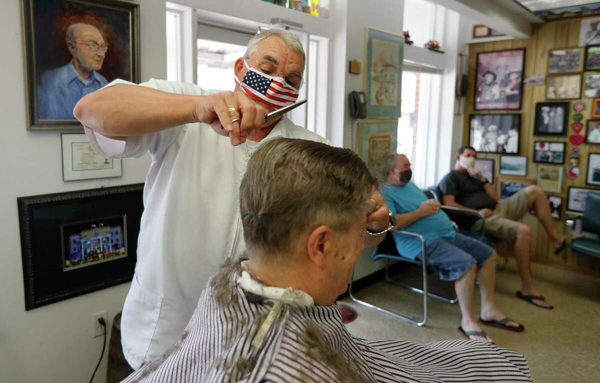 Owner Leon Apostolo cut the hair of Joe Whisenant at Shepard's Barber Shop, Friday, May 8, 2020, in Conroe. Gov. Greg Abbott modified his initial executive order to reopen the Texas economy on Tuesday to allow barbershops, nail salons and hairdressers to reopen Friday with some social distancing and hygiene protocols.