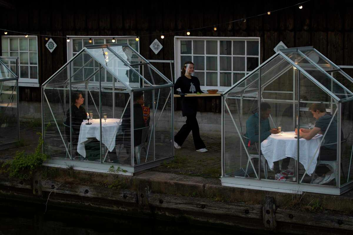 Staff at the Mediamatic restaurant serve food to volunteers seated in small glasshouses during a try-out of a setup which respects social distancing abiding by government directives to combat the spread of the COVID-19 coronavirus in Amsterdam, Netherlands, Tuesday, May 5, 2020.
