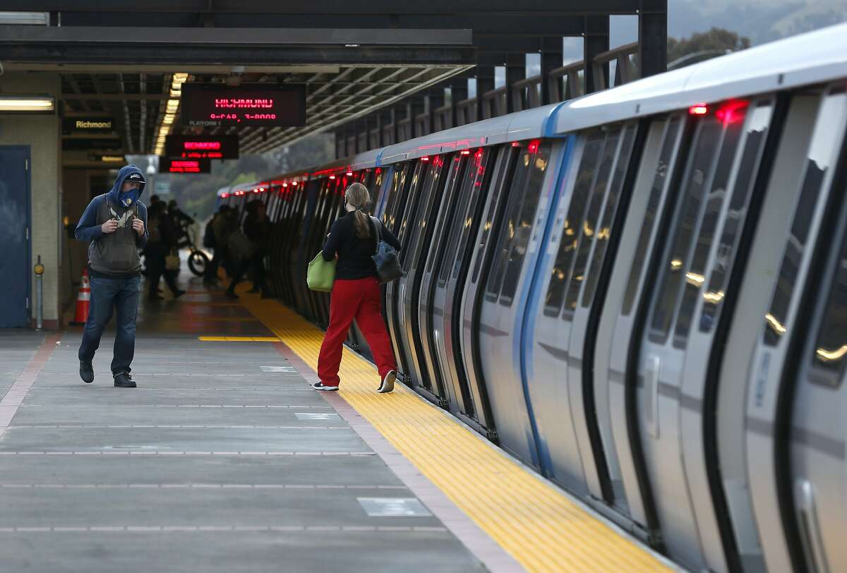 Commuters board and leave a Richmond-bound train at the MacArthur BART station in Oakland, Calif. on Tuesday, May 12, 2020. BART is joining transit agencies from around the country in seeking economic federal relief funds because of dwindling ridership during the coronavirus shutdown.