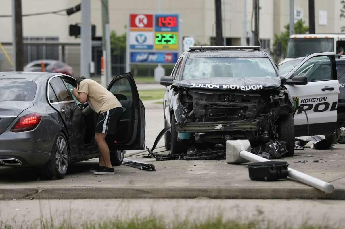 A man looks into a vehicle at the scene where a police cruiser and that vehicle collided during a police pursuit Tuesday, May 12, 2020, in Houston. The driver being pursued, in another vehicle, fled to a nearby home, and officers apprehended him after a short foot chase.