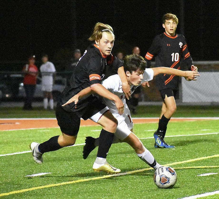 Edwardsville forward Cooper Nolan, left, battles for the ball with Alton's Coleton Sebold during a game last season. Nolan has verbally committed to play at Lewis and Clark Community College next season. Photo: Matt Kamp | For The Telegraph