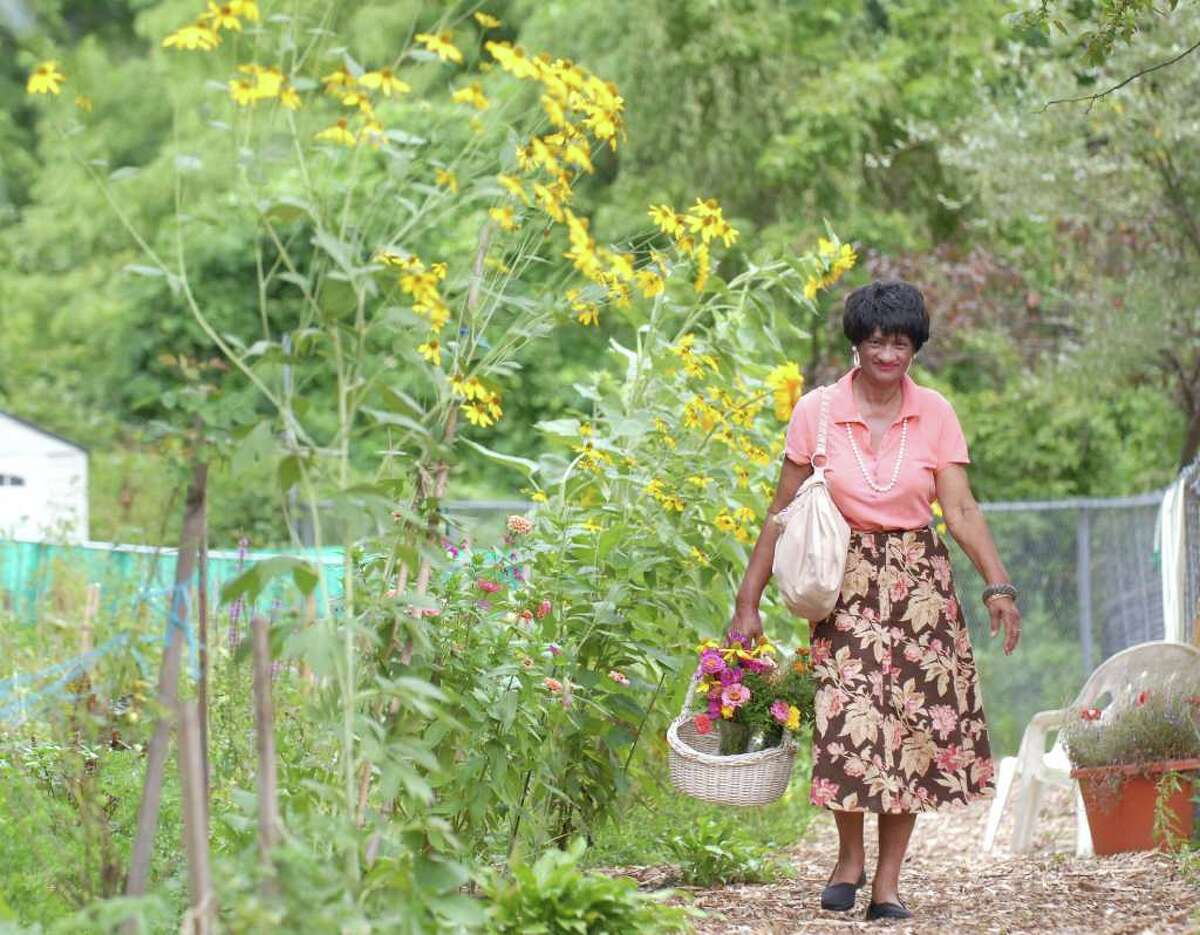 Gardener Jessie Ramnath walks through the Armstrong Court Community Garden with a basket full of flowers she grew in the garden which she was donating as decorations for