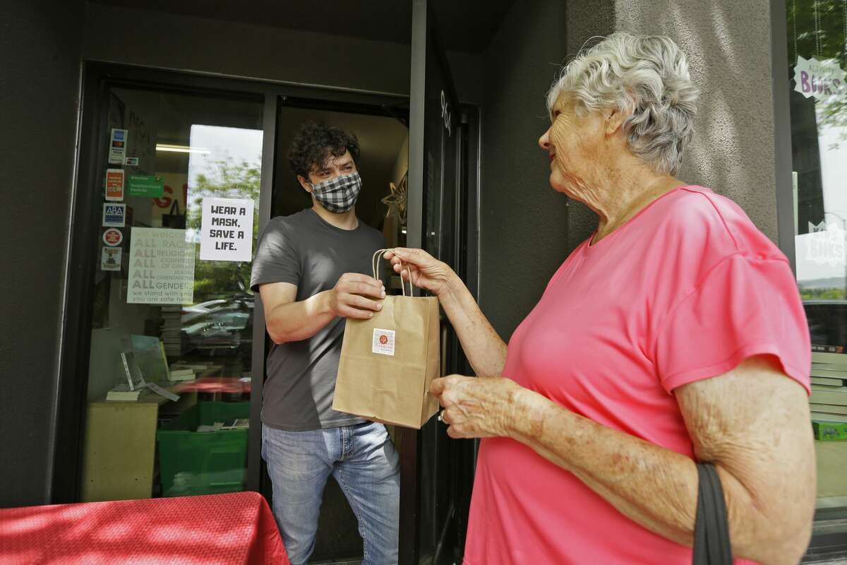 Gail Harrison picks up a book she purchased from Paul Leavitt at the Napa Bookmine store Friday, May 8, 2020, in Napa, Calif. Some California retailers and manufacturers were able to reopen Friday under a new plan by Gov. Gavin Newsom aimed at easing the state's stay-at-home coronavirus order.
