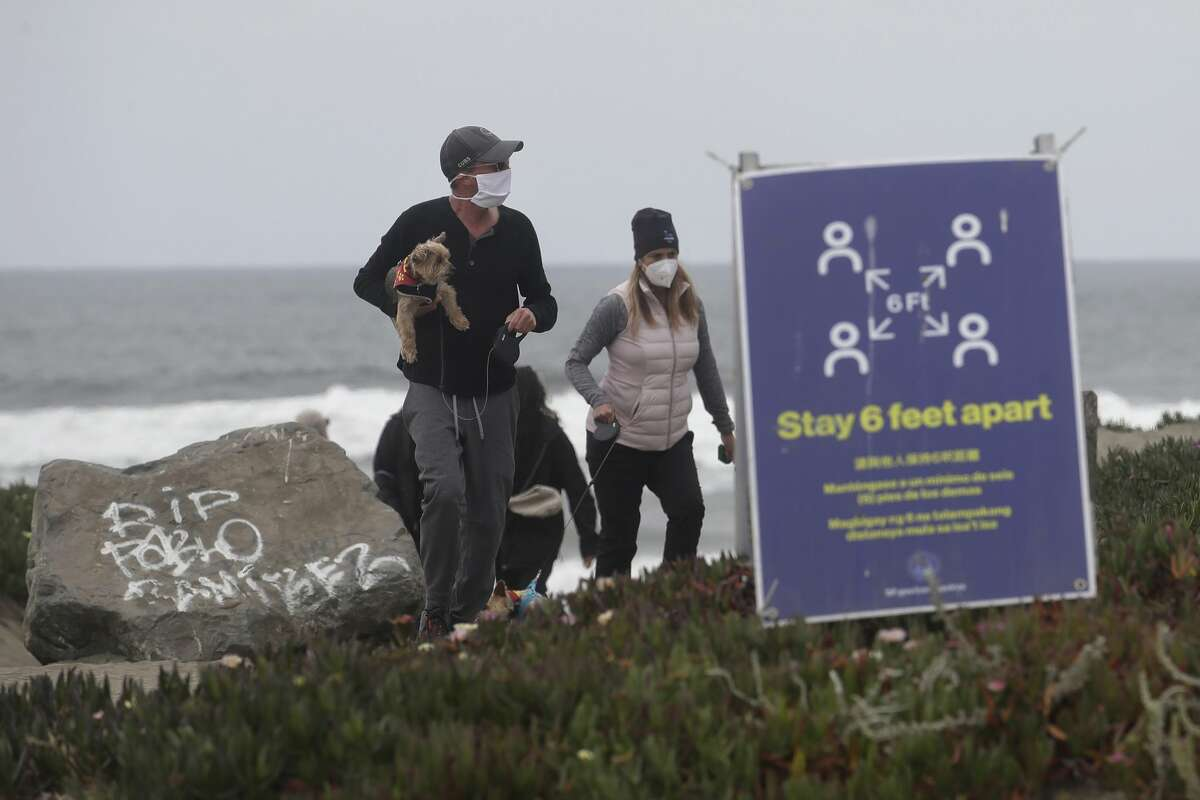 Chris McDonnell, left, and his wife, Pamela, wear face masks while walking their dogs on a closed stretch of The Great Highway at Ocean Beach during the coronavirus outbreak in San Francisco, Sunday, May 10, 2020.