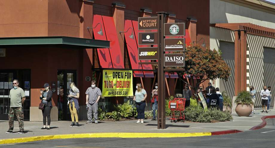 People wear masks as they socially distance themselves from one another while waiting in line to enter a grocery store on Thursday, May 7, 2020, in Alameda, Calif. Photo: Ben Margot/Associated Press / Copyright 2020 The Associated Press. All rights reserved.