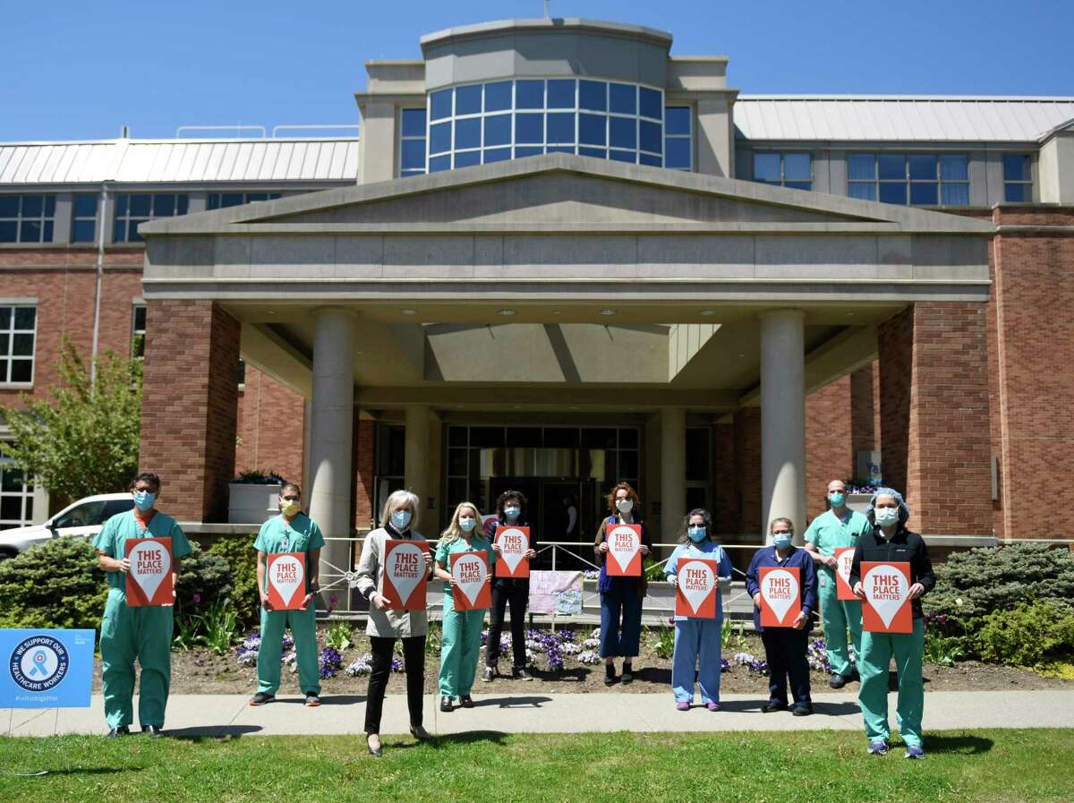 Greenwich Historical Society leadership and hospital workers hold