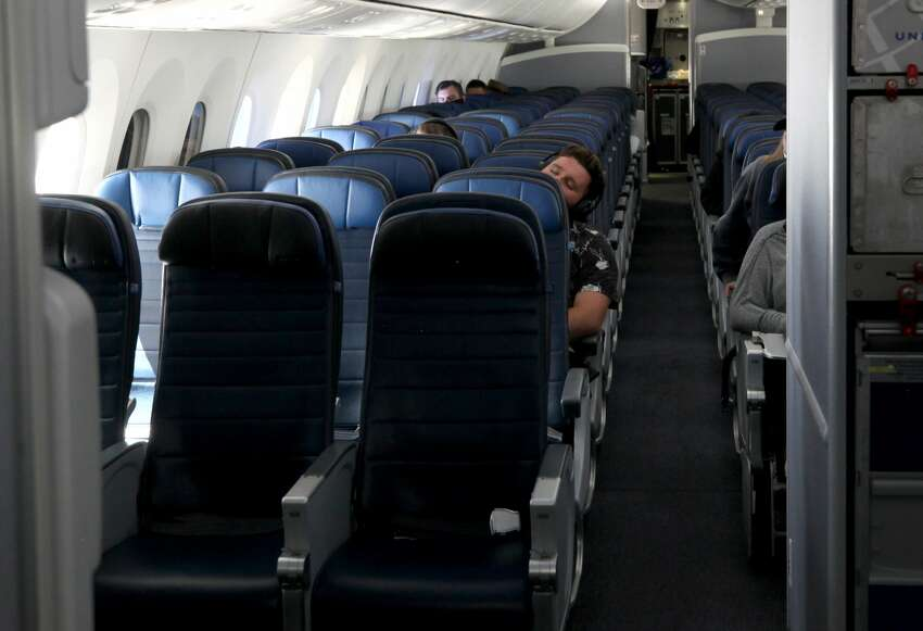 A passenger sleeps aboard a United Airlines flight to Houston, Texas from San Francisco on May 11, 2020. Air travel is down as estimated 94 percent due to the coronavirus (COVID-19) pandemic, causing U.S. airlines to take a major financial hit with losses of $350 million to $400 million a day and nearly half of major carriers airplanes are sitting idle.