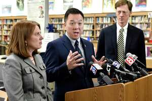 Connecticut Attorney General William Tong, center, New Haven Mayor Justin Elicker, right, and Connecticut Consumer Protection Commissioner Michelle Seagull, left, speak at Hillhouse High School in New Haven, Conn. Tong and Seagull announced March 24, 2021 that Connecticut would receive about $1.8 million through a 47-state settlement with medical-device manufacturer Boston Scientific.