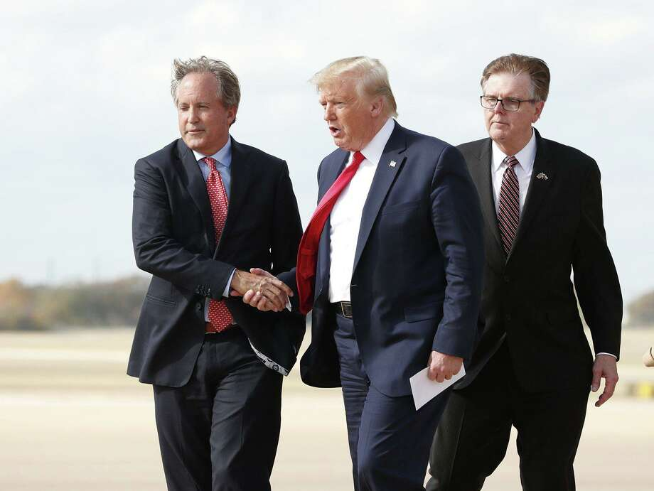 """Donald Trump greets Texas Attorney General Ken Paxton (left) as Lt. Gov. Dan Patrick follows at Austin Bergstrom International Airport in 2019. Paxton recently blasted several coronavirus restrictions in San Antonio and Bexar County as """"unlawful and unconstitutional."""" Photo: Austin American-Statesman"""