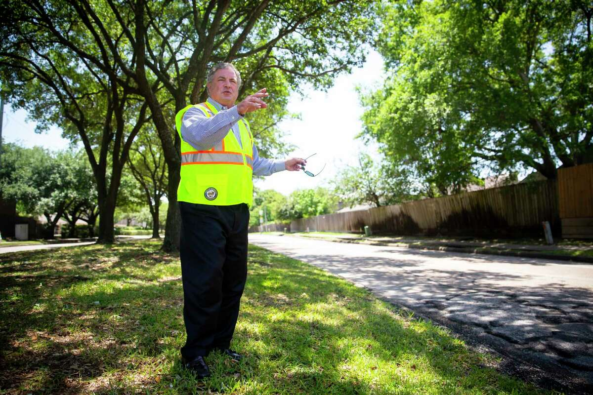 Houston District G Councilman Greg Travis surveys road damage along the median on Kirkwood on May 11, 2020. A long-delayed project will rebuild the street and drainage, but preserve most of the street's trees.