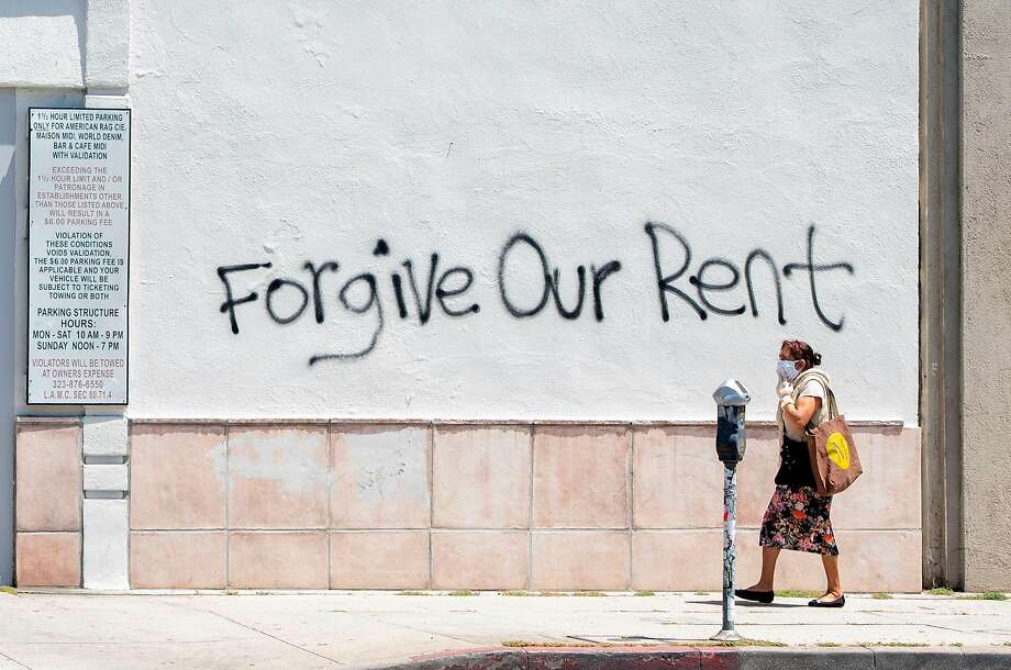 A woman wearing a mask walks past a wall bearing a graffiti asking for rent forgiveness on La Brea Ave in Los Angeles. Photo: Valerie Macon / AFP / Getty Images