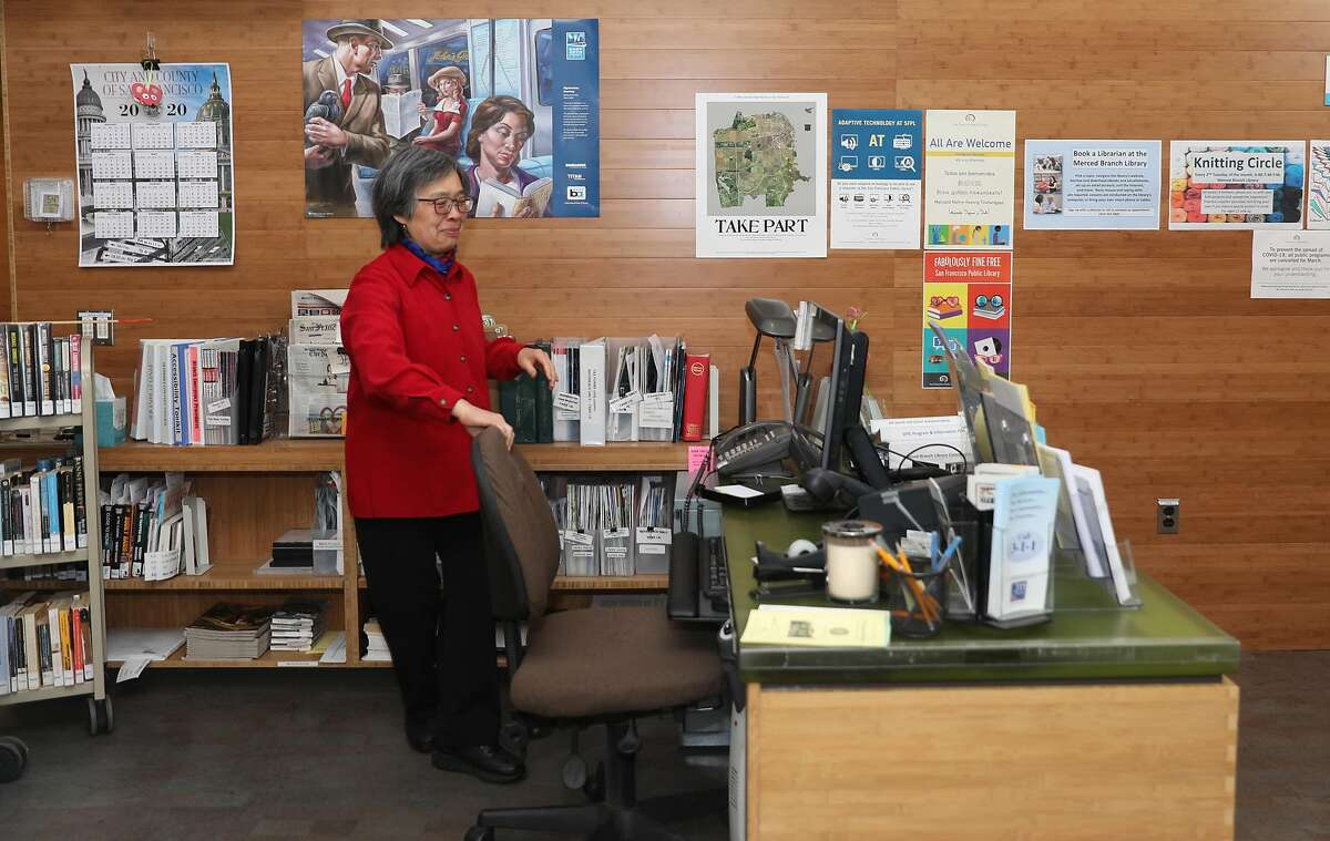 Jensa Woo has been a librarian for the past 40 years and tidies her desk at the SF Public Library Merced Branch which is presently closed as she visits it on Tuesday, May 12, 2020, in San Francisco, Calif. UCSF is helping California dramatically scale up its coronavirus contract tracing efforts with a new workforce training program that will recruit up to 20,000 individuals including Jensa Woo.