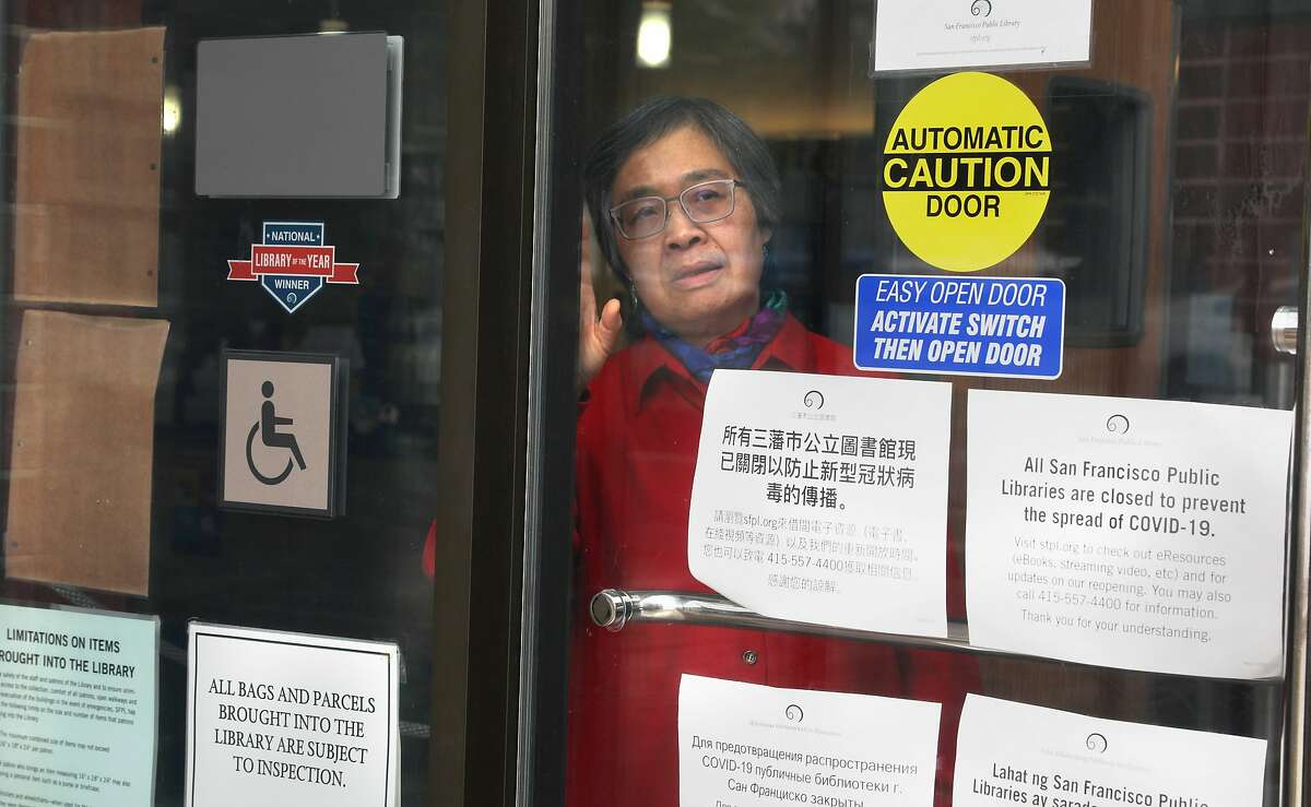 Jensa Woo has been a librarian for the past 40 years and looks through the window at the SF Public Library Merced Branch which is presently closed as she visits it on Tuesday, May 12, 2020, in San Francisco, Calif. UCSF is helping California dramatically scale up its coronavirus contract tracing efforts with a new workforce training program that will recruit up to 20,000 individuals including Jensa Woo.