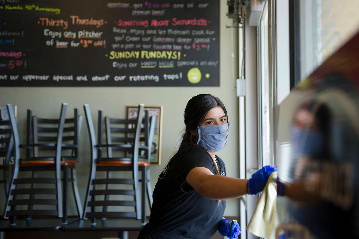 Server Alexis Quirarte of Yuba City sanitizes the front door before opening Midtown Grill in Yuba City, Calif. on Wednesday, May 6, 2020.